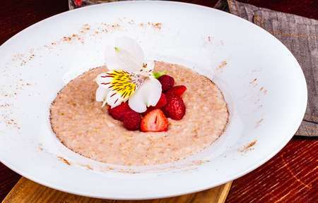 Oatmeal porridge with strawberries and raspberries in a white plate. Healthy food