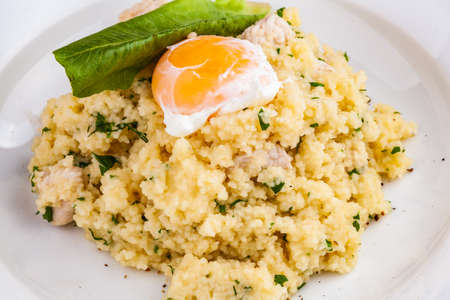 Couscous with chicken and egg on a white plate
