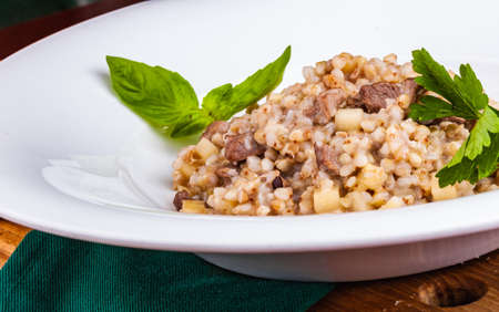 Buckwheat with duck meat and apple on white plate