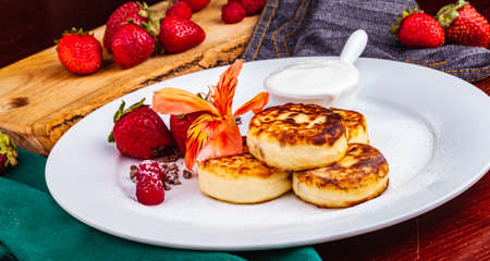 Breakfast. Cottage cheese pancakes, syrniki, curd fritters with fresh berries raspberry and strawberry, sour cream on white plate. Russian or Ukrainian cuisine. Standard-Bild