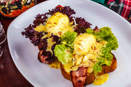 Eggs Benedict with bacon, hollandaise sauce on toasted bread