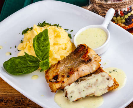 Fried fish with mashed potatoes on white plate Standard-Bild