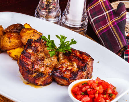 Grilled meat with baked potato and tomato on white plate
