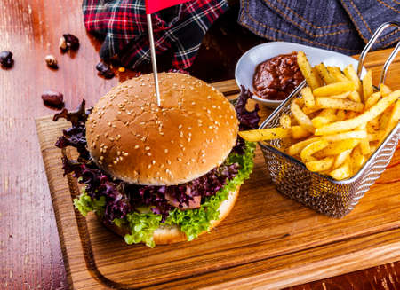 Hamburger with basket of French fries on and tomato sauce on wooden cutting board