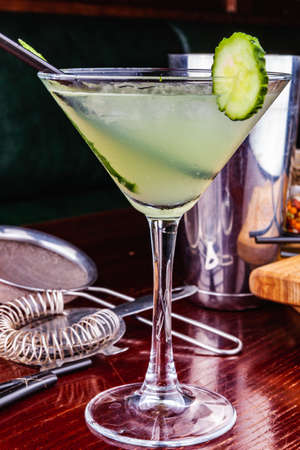 Cucumber martini cocktail on wooden table Standard-Bild