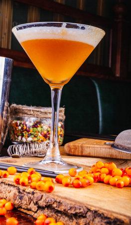 Ð¡ocktail with sea buckthorn in martini glass on wooden table Standard-Bild