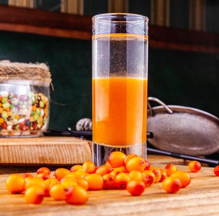 Ð¡ocktail with sea buckthorn on a wooden table