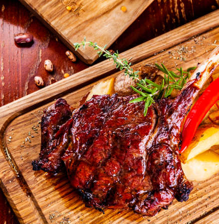 Grilled meat and vegetables on wooden cutting board