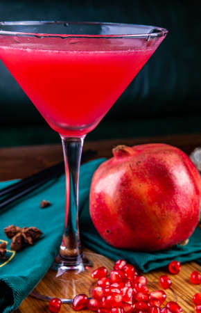 Pomegranate cocktail in martini glass on wooden table. Close up Standard-Bild