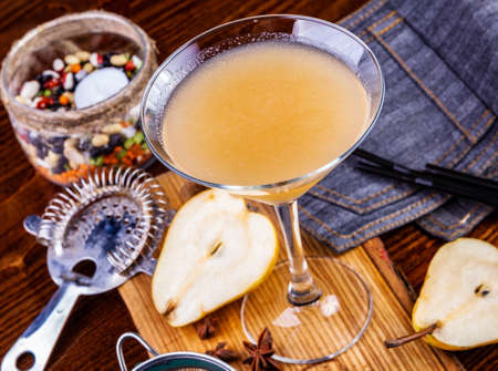 Pear cocktail in martini glass on wooden table. Close up Standard-Bild