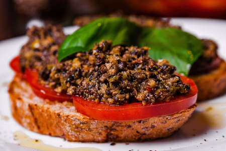 Bruschetta with capers, olives and tomatoes on a white plate