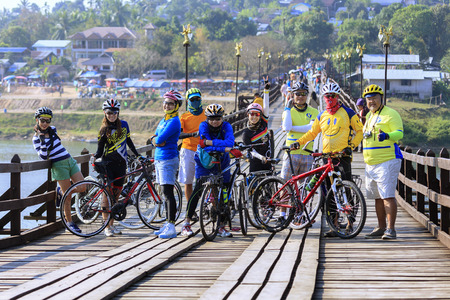 race for time: Sangkhlaburi, Thailand - January 24, 2015: Cyclists are on the wooden bridge , The Bridge across the river. It s called Saphan Mon at SANGKHLABURI, THAILAND.