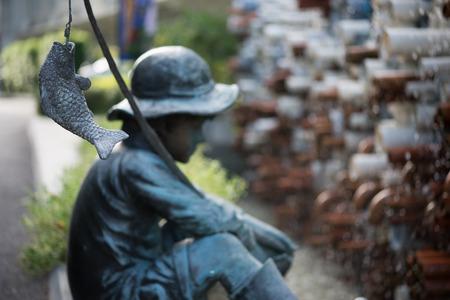 waterwheel: Sculpture of Little boy fishing in the garden.