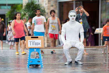 catalunya: PHUKET, THAILAND - October 3, 2015: Street Performer imitating white statue sitting on a chair with a tip box  in the Jungceylon shopping mall Phuket, Thailand.