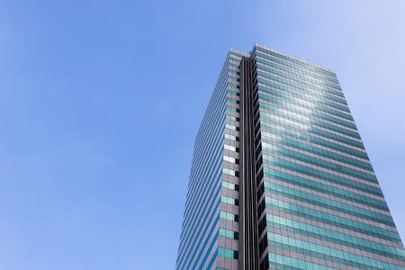 Modern office building against clear blue sky.