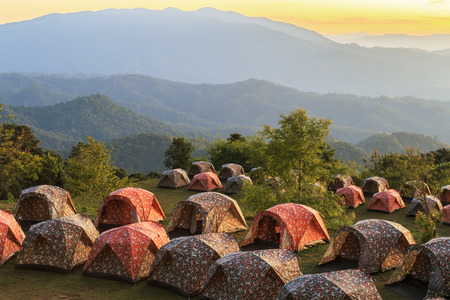 roughing: Camping tents in mountains during sunset.