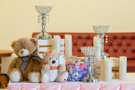 Wedding decoration with sweets, toy bears, rings and candlestick.