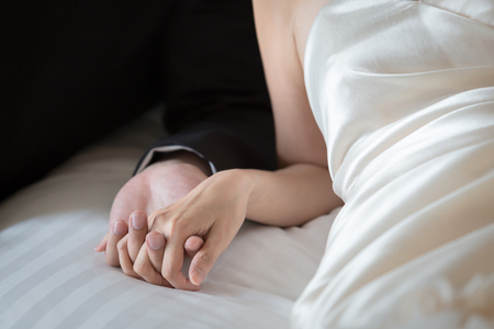dinner jacket: Bride and groom holding hands on a bed. Stock Photo