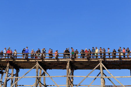 icon idea idiom illustration: Sangkhlaburi, Thailand - February 14, 2016: Crowd of tourist are enjoying on wooden bridge against clear blue sky. Editorial