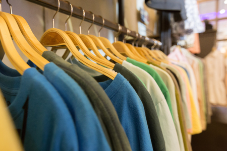 closet rod: T-shirts hanging on wooden hangers. Stock Photo