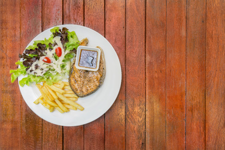 Grilled salmon steak, Serve with french fries and salad vegetables in white plate on wooden panel background.