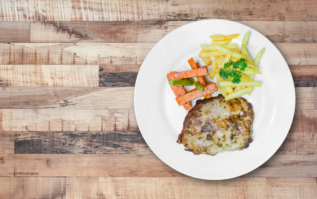 pork  loin: Grilled pork loin steaks, serve with french fries and vegetables in white plate on wooden table background. Stock Photo