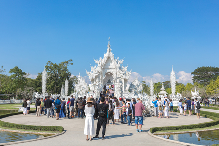 Chiang Rai, Thailand - January 22, 2017: Unidentified tourists are at Wat Rong Khun or White Temple, Landmark in Chiang Rai, Thailand. -This is a contemporary unconventional Buddhist temple.