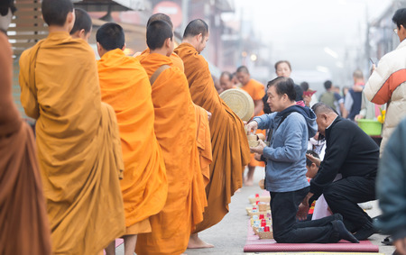 Chiang Khan, Thailand - December 12, 2016: Unidentified people offerings food to Buddhist monks. Thailand. Thai traditional, people will make merit making by give food to monk.