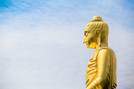 The big Buddha statue against cloudy and blue sky background.