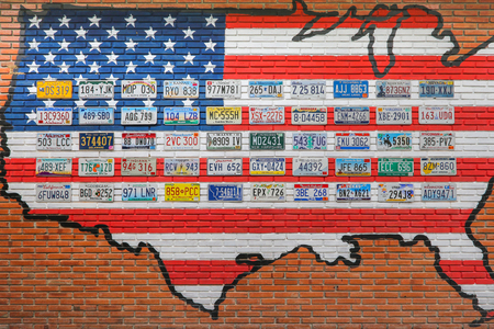 Ratchaburi, Thailand - December 15, 2016: Various old American license plates from different states on the wall of brick building in Thailand.
