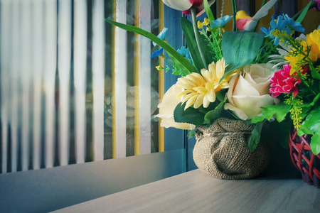 Vase with artificial multicolored flowers beside the window. - Vintage style