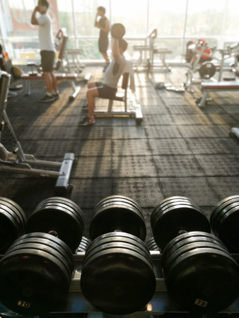Rows of dumbbells and unidentified people are working out in the fitness gym.