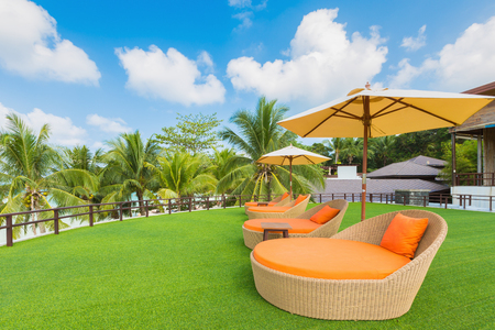 Rattan weave daybed chair on top green grass floor near the tropical white sand beach in Thailand. With the aqua colored water reaching to the horizon.