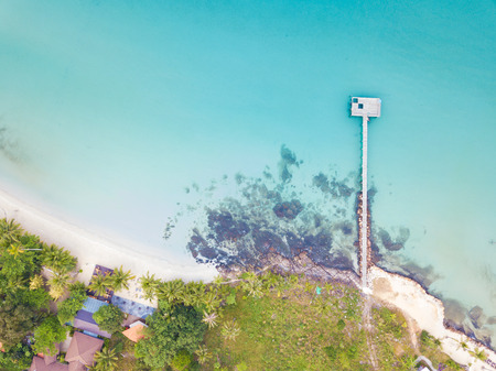 Aerial view of beautiful tropical resort beach with wooden pier into the sea.