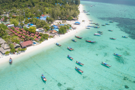 Aerial view of Resorts and boats on tropical white sand at Sunrise Beach, Lipe Island, Thailand.