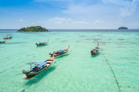 Aerial view over group of long tail boats with beautiful sea and beachTop view from drone Koh Lipe island, Satun Province, Thailand. Фото со стока