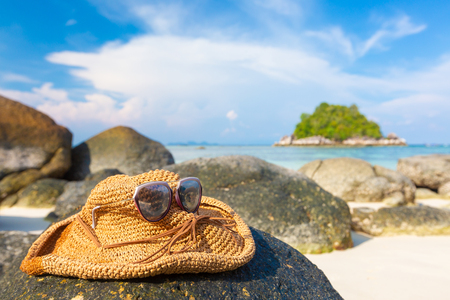 Focus on Weave hat and sunglasses on rock white sand beach. - You can use for Holiday, Vocation, Travel, Lifestyle and Relax concept.