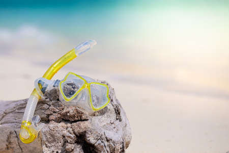 Snorkel equipment snorkeling mask tube lying on stone beach sea shore. Summer vacation swimming fun concept.