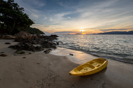 Dramatic sunset over Beach at Lipe Island, Thailand, with kayak boat in the foreground. Фото со стока