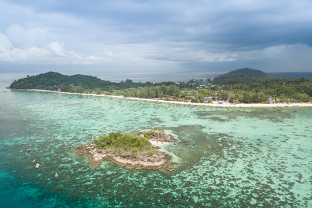 Aerial view of beautiful tropical beach in Satun, Thailand. Lipe island is the Thai island in the Andaman Sea. Which is populated with small islands and known for its coral-rich waters. Фото со стока