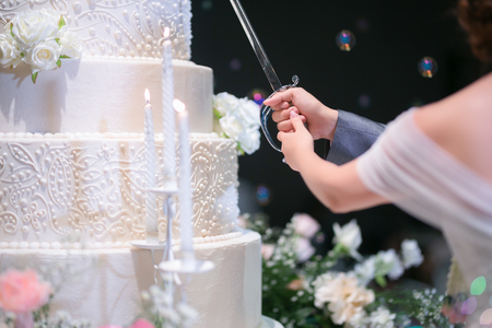 Close up to a part of body of bride and groom are cutting their wedding cake.