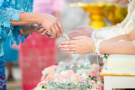Guest pouring water with bride and groom hands in water relaunch ceremony. Thai traditional wedding.