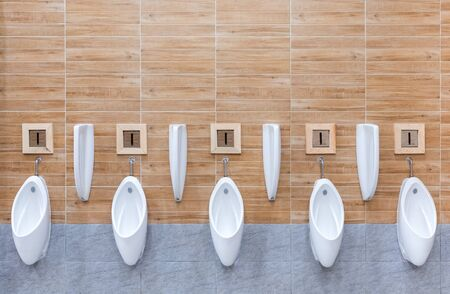 Urinals men public toilet Closeup white urinals in mens bathroom design of white ceramic urinals for men in toilet room. Zdjęcie Seryjne