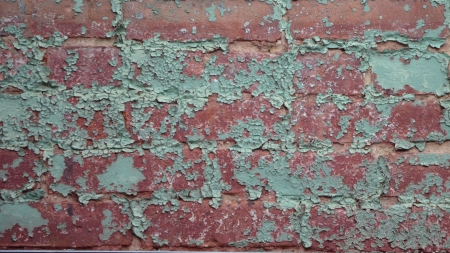 chipped paint: Old red brick wall with green chipped paint