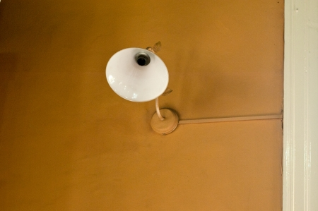 white wall lamp without bulb on a brown wall Stock Photo
