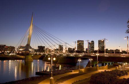 Foto van de avond van Esplanade Reil brug en de binnenstad van Winnipeg  Redactioneel