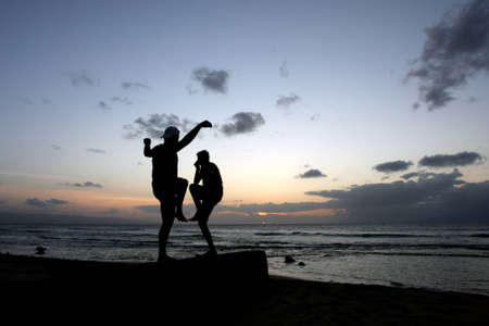 teenage boys doing karate poses at sunset by the ocean photo