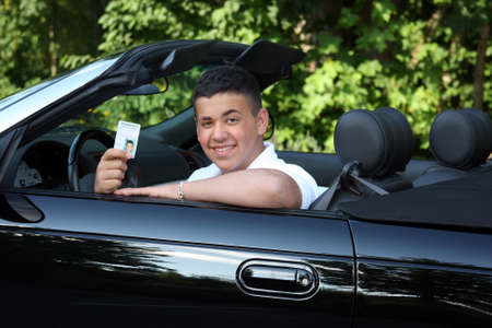 teenage boy with drivers license in black convertible