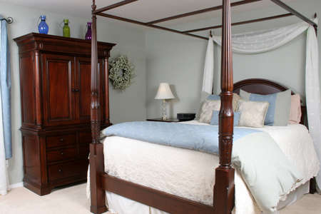 four poster bed: Bedroom with four poster bed and cherry furnishings Stock Photo