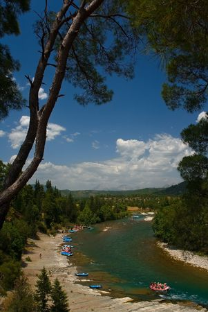 mountain river with pine trees and rafting boats photo